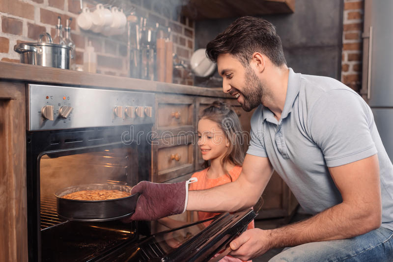 Smiling father and daughter taking cake from oven. `Side view of smiling father and daughter taking cake from oven stock photography