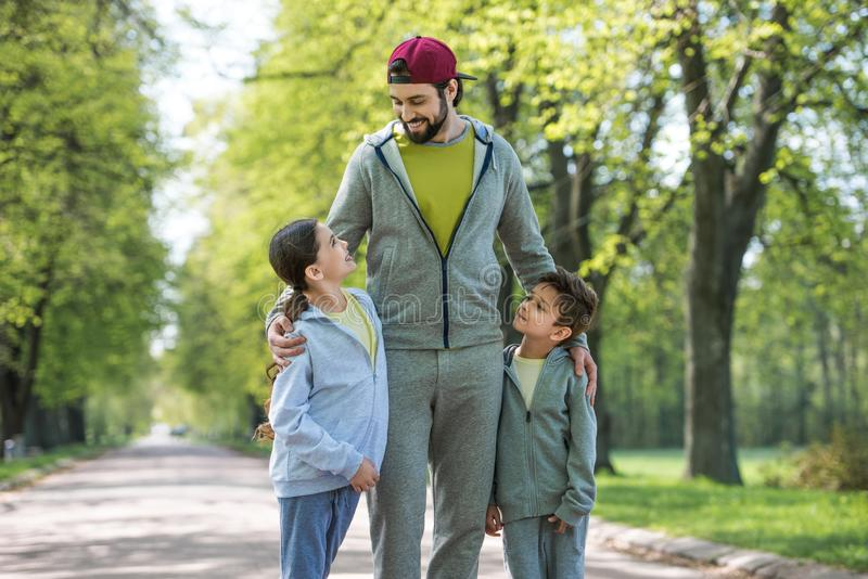 smiling father embracing daughter and son royalty free stock photo