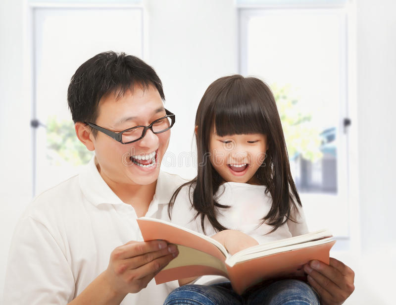 Smiling father and her daughter reading a book. At home royalty free stock image