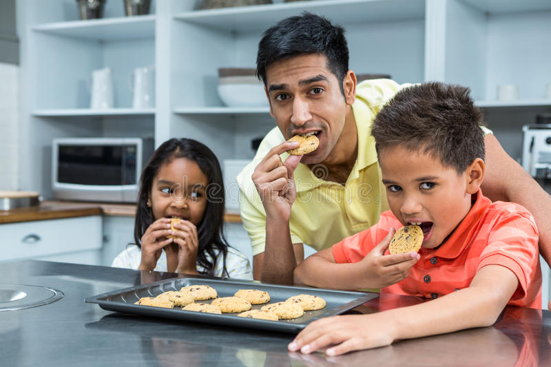 Smiling father with his children eating biscuits. In the kitchen at home stock image
