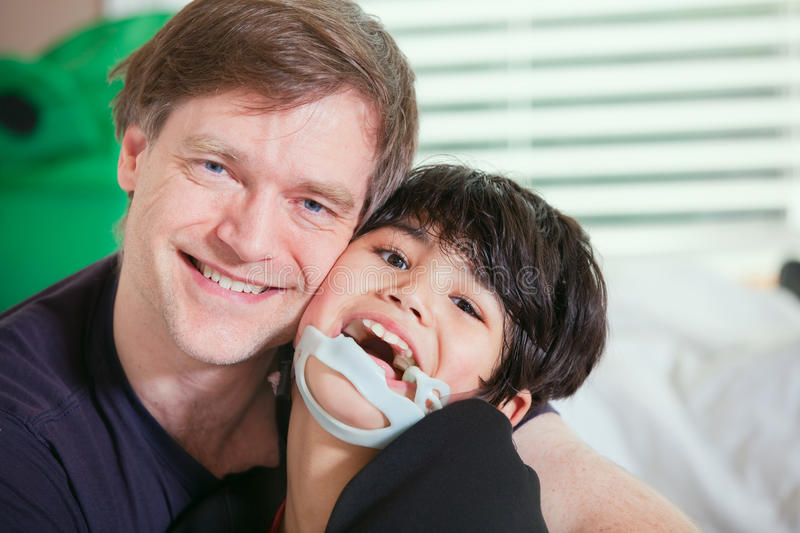 Smiling father holding disabled son royalty free stock photo