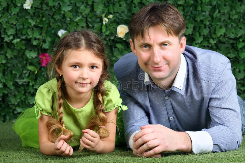 Smiling father and little daughter lie on green lawn
