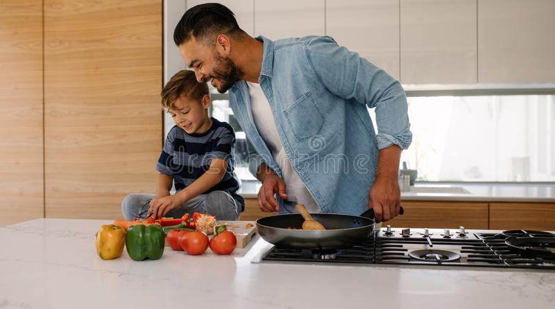 Father and son cooking together in kitchen stock photo