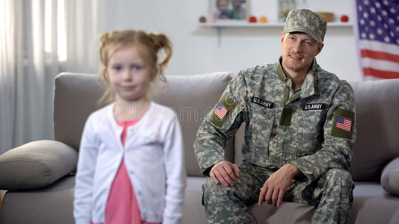 Smiling father military officer looking at grown up daughter with pride, us flag. Stock photo royalty free stock photos
