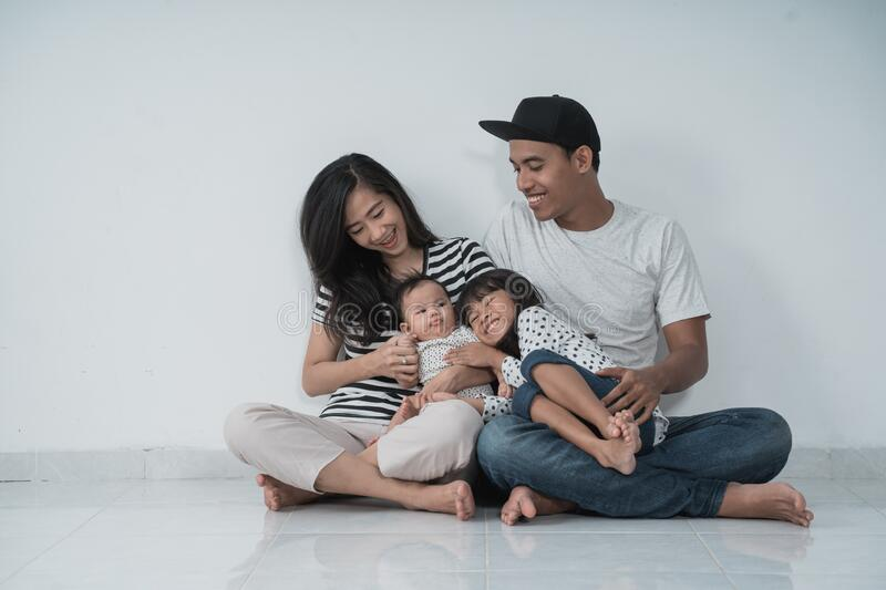 Smiling father,mother,and daughter looking to her baby stock photography