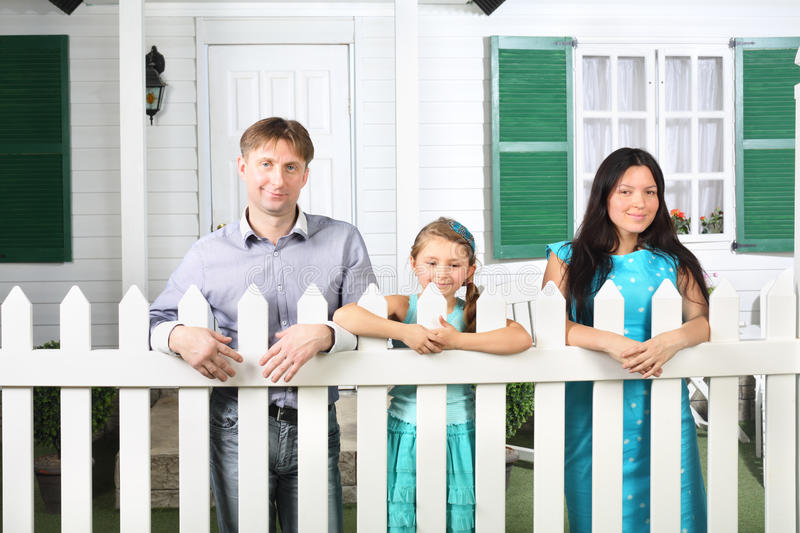 Smiling father, mother and little daughter stand next to fence stock image