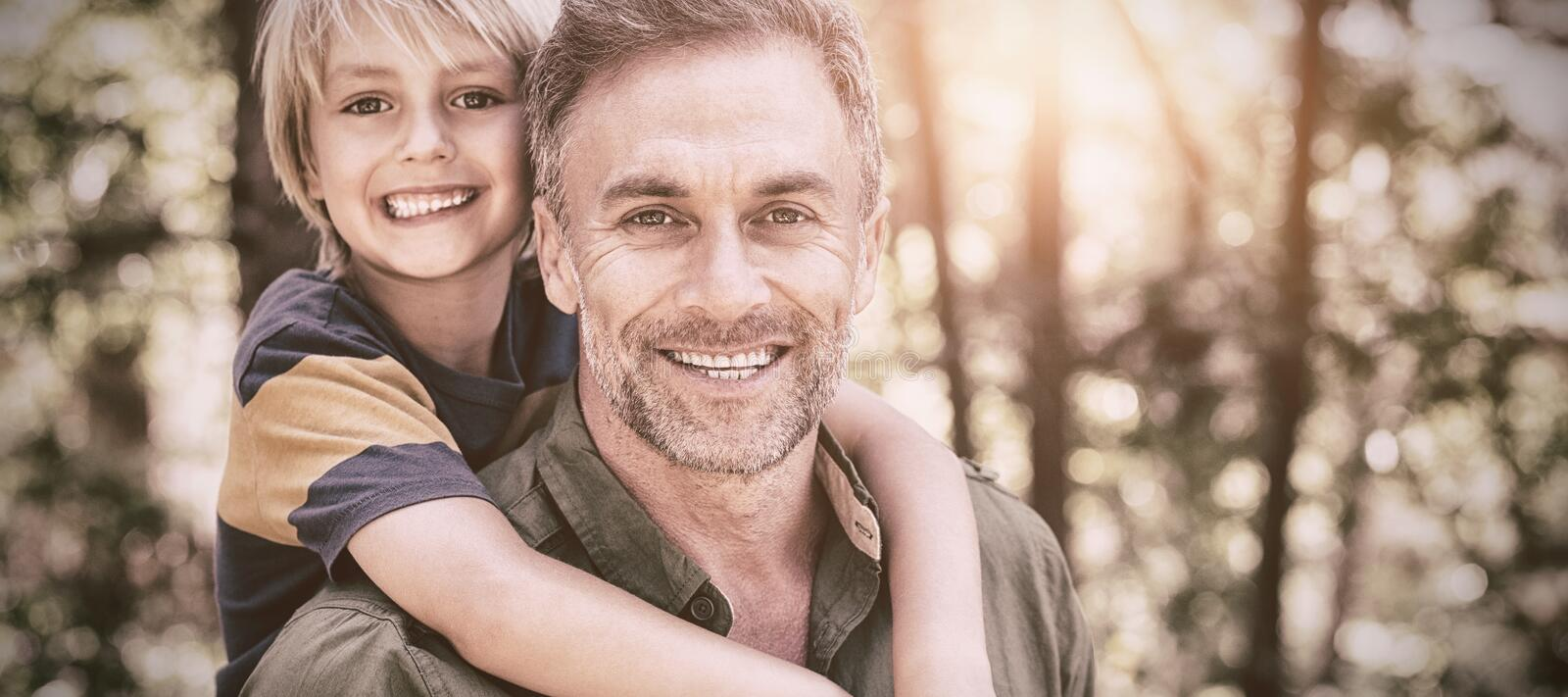 Smiling father piggybacking son in forest. Portrait of smiling father piggybacking son in forest stock photography