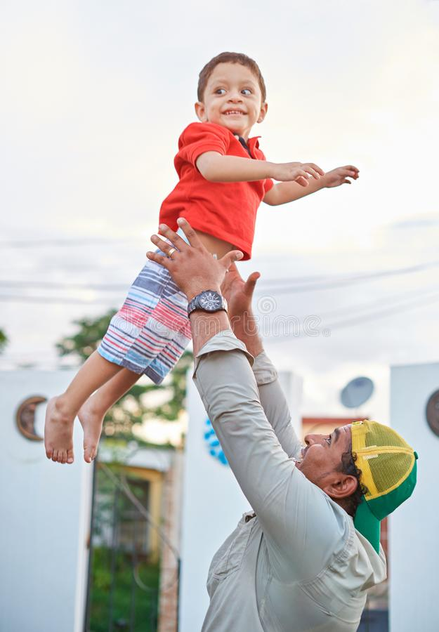 Smiling father playing with his son royalty free stock images