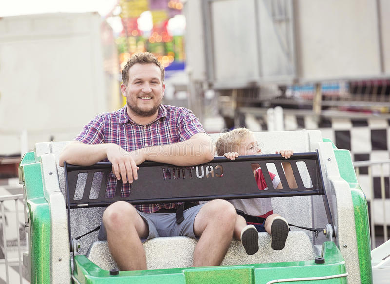 Smiling father and son on an Amusement Park Ride together stock photography