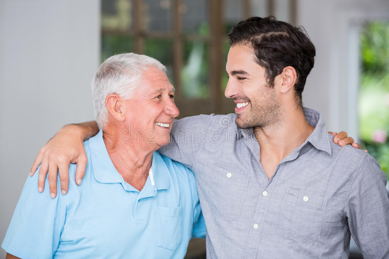 Smiling father and son with arm around. Wile standing at home royalty free stock photography