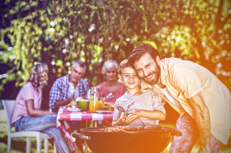 Smiling father with son by barbecue grill in yard. Smiling father with son by barbecue grill against family in yard stock photography
