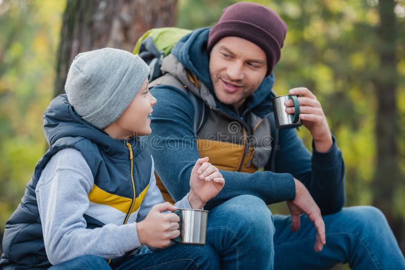Smiling father and son drinking tea from thermos. In autumn forest royalty free stock image