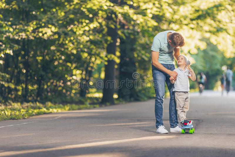 Smiling father and son in the park stock images