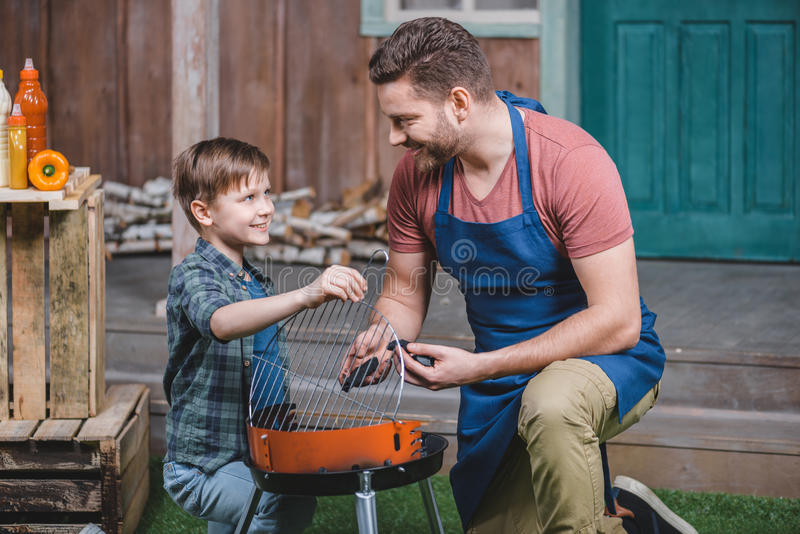 Smiling father and son preparing grill for barbecue. Side view of smiling father and son preparing grill for barbecue royalty free stock photography