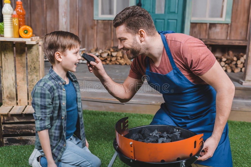 Smiling father and son preparing grill for barbecue. Side view of smiling father and son preparing grill for barbecue stock photos