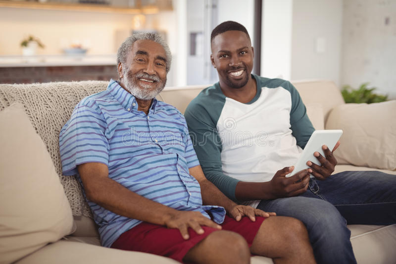 Smiling father and son sitting on sofa with digital tablet in living room. Portrait of smiling father and son sitting on sofa with digital tablet in living room stock image