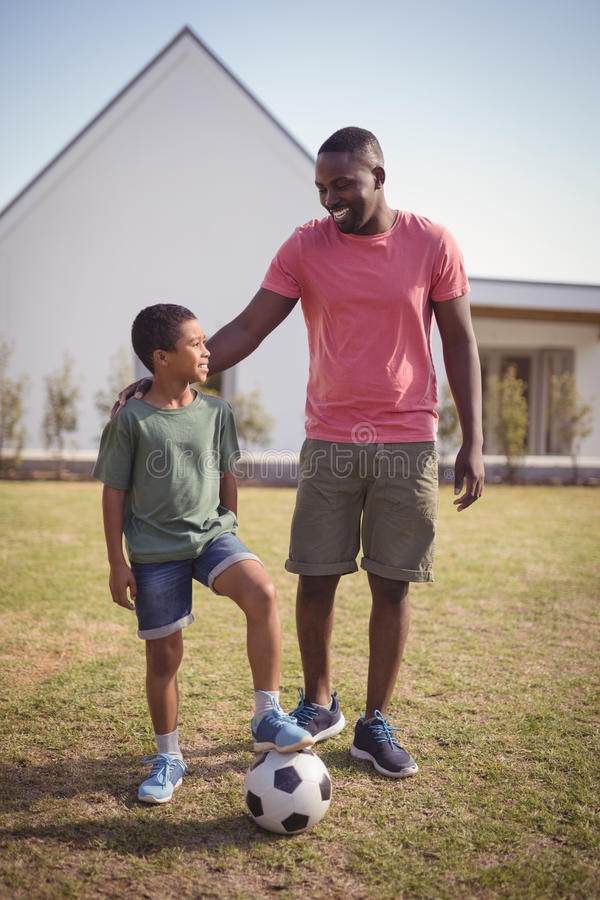 Smiling father and son standing in garden with football royalty free stock image