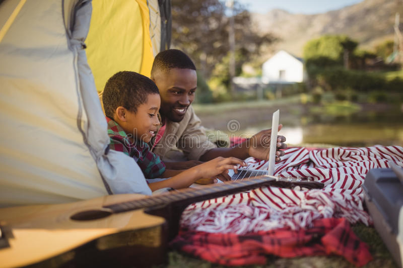 Smiling father and son using laptop in tent. At park stock photography