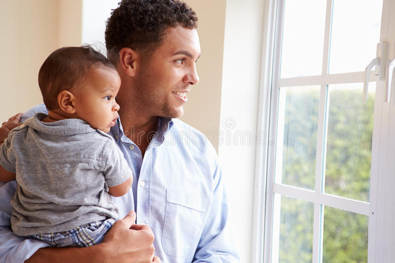 Smiling Father Standing By Window With Baby Son At Home royalty free stock photos