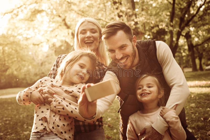 Smiling father taking self portrait of his family in park. royalty free stock photos