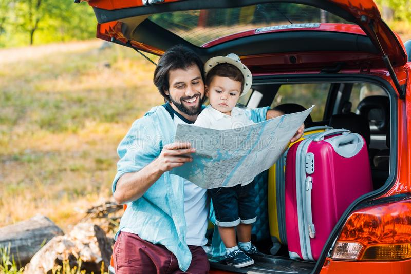Smiling father and toddler son looking at map. At car trunk stock photos