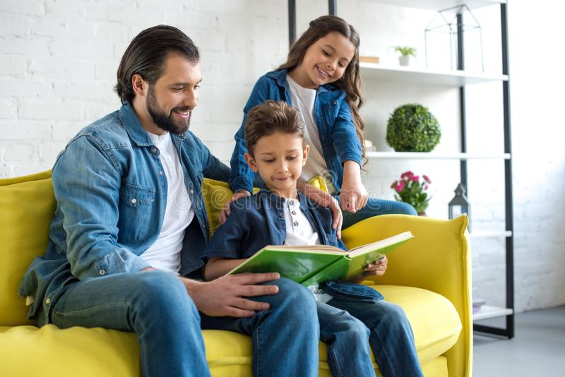 Smiling father with two kids reading book together while sitting on couch. At home royalty free stock photography