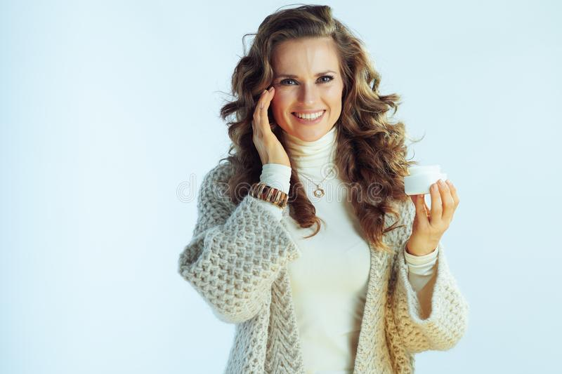 Smiling female applying facial creme as part of winter skincare. Smiling young female with long wavy hair in neck sweater and cardigan applying facial creme as stock photos