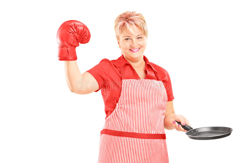 Smiling female with apron and red boxing glove holding a frying. Smiling mature female with apron and red boxing glove holding a frying pan isolated on white stock photos