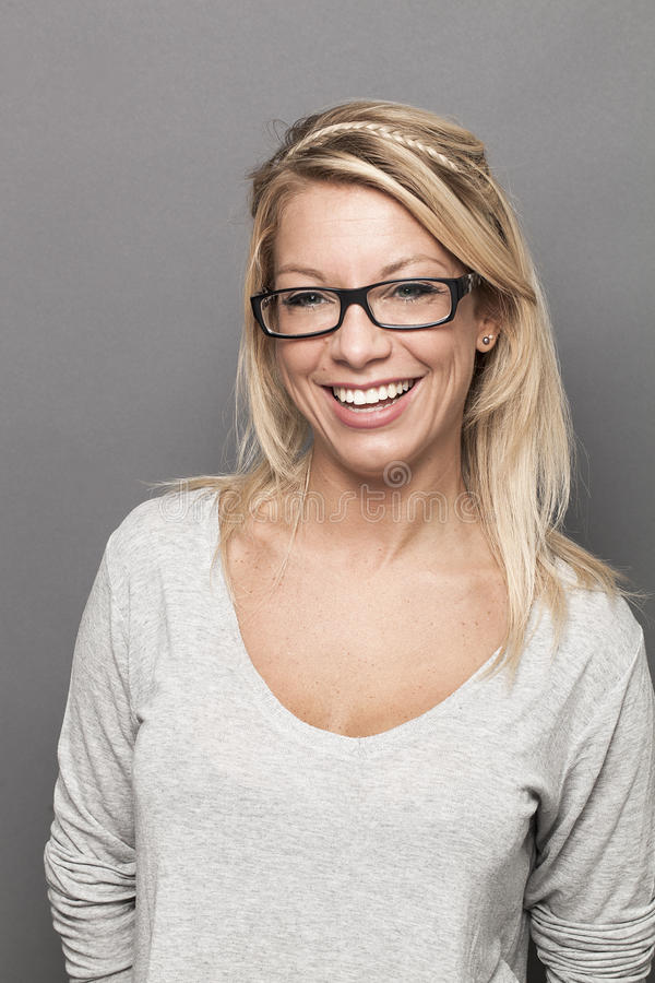 Smiling female blond student expressing wellbeing at studying. Natural smile - young blond woman with serious eyeglasses laughing expressing happiness and stock images