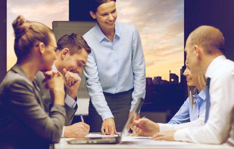 Smiling female boss talking to business team royalty free stock photography