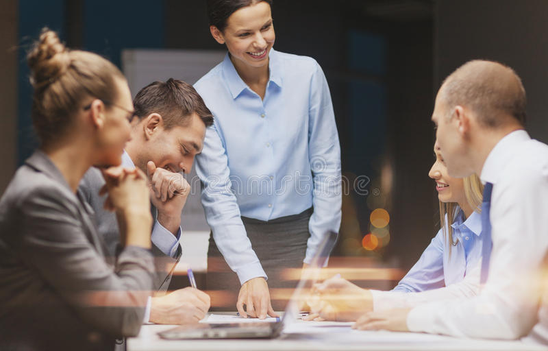 Smiling female boss talking to business team stock photo