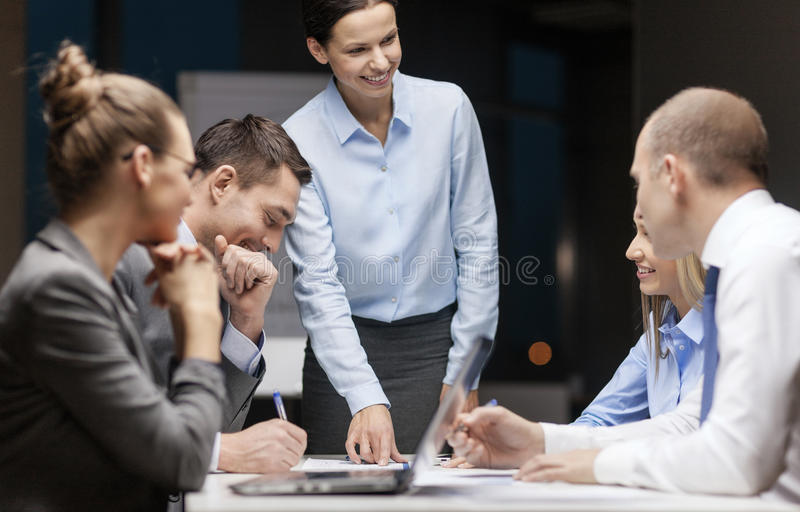 Smiling female boss talking to business team stock image