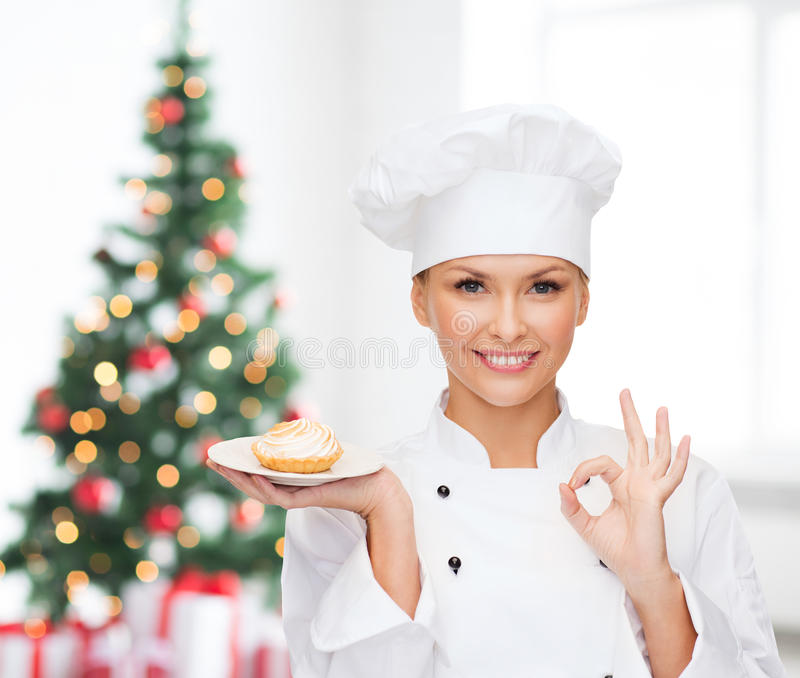 Smiling female chef with cupcake on plate royalty free stock photos