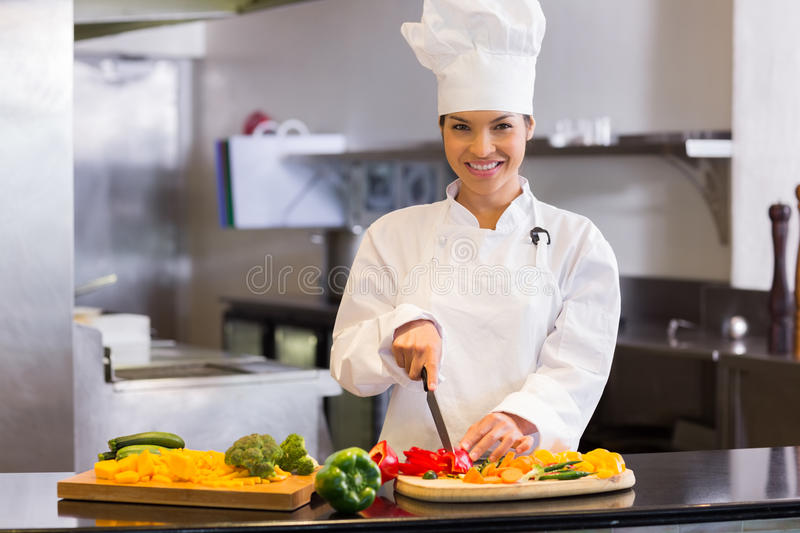 Smiling female chef cutting vegetables in kitchen royalty free stock images