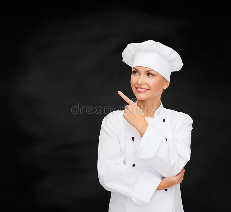 Smiling female chef pointing finger to something royalty free stock photo