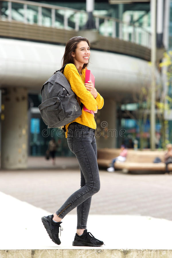 Smiling female college student walking to class with bag. Portrait of smiling female college student walking to class with bag stock photography