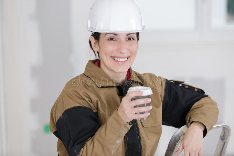 Smiling female construction worker having coffee break royalty free stock images