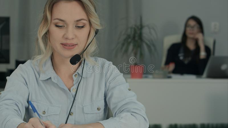 Smiling female consultant with headset making notes while her coworker taking selfies stock image