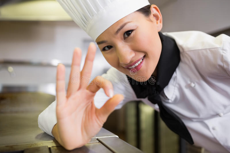 Smiling female cook gesturing okay sign in kitchen. Closeup portrait of a smiling female cook gesturing okay sign in the kitchen royalty free stock photo