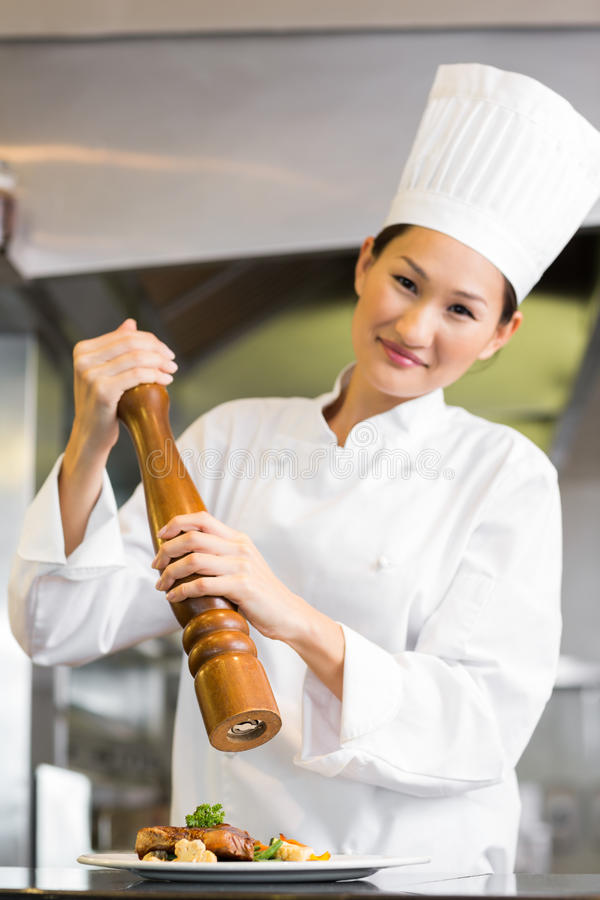 Smiling female cook grinding pepper on food in kitchen. Portrait of a smiling female cook grinding pepper on food in the kitchen royalty free stock photography