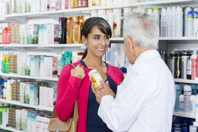 Customer Looking At Senior Chemist Holding Product By Shelves stock photography