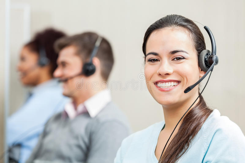 Smiling Female Customer Service Agent In Office. Portrait of smiling female customer service agent with colleagues in background at office stock image