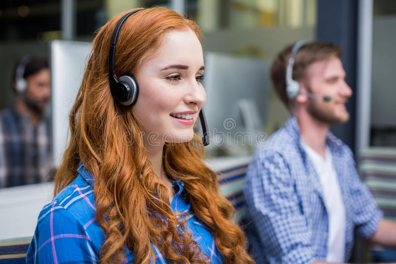 Smiling female customer service executive talking on headset at desk. In office stock photo