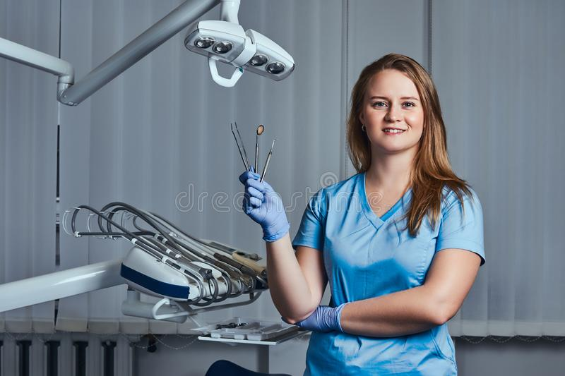 Female dentist holding dental tools while sitting in her dentist office. stock images
