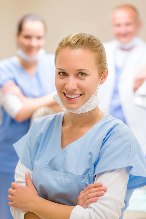 Smiling female dentist surgeon with colleagues stock images
