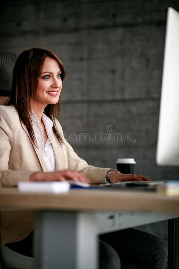 Smiling female designer using computer in office stock images