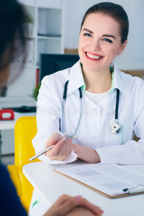 Smiling female doctor consulting patient how to fill application form . Female doctor consulting patient how to fill application form. Physical, problem exam stock photography
