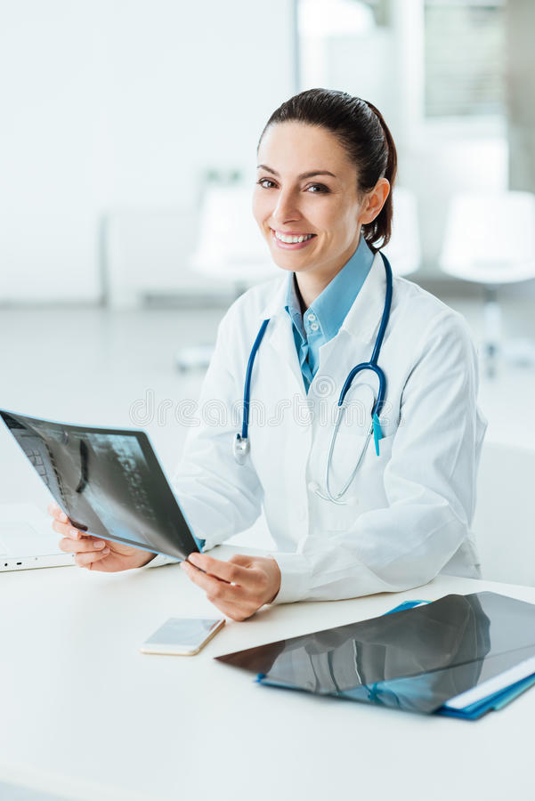 Smiling female doctor examining an x-ray stock photos