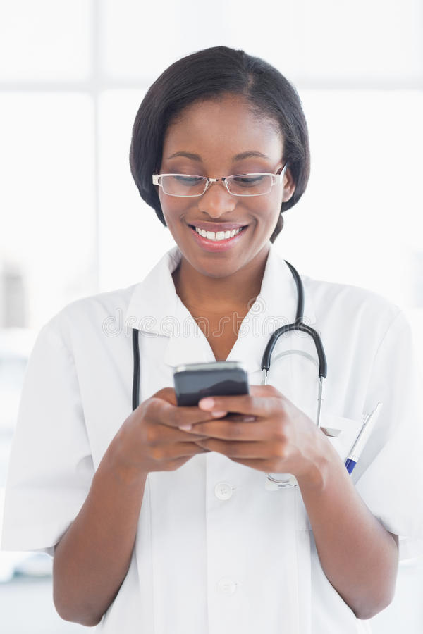 Smiling female doctor holding a mobile phone. In the hospital stock photos