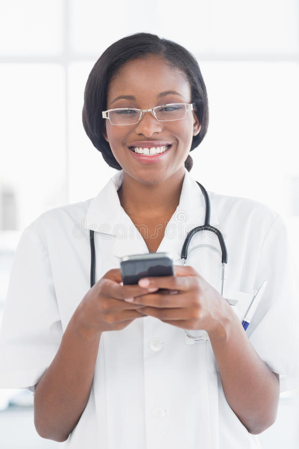 Smiling female doctor holding a mobile phone. In the hospital royalty free stock photo